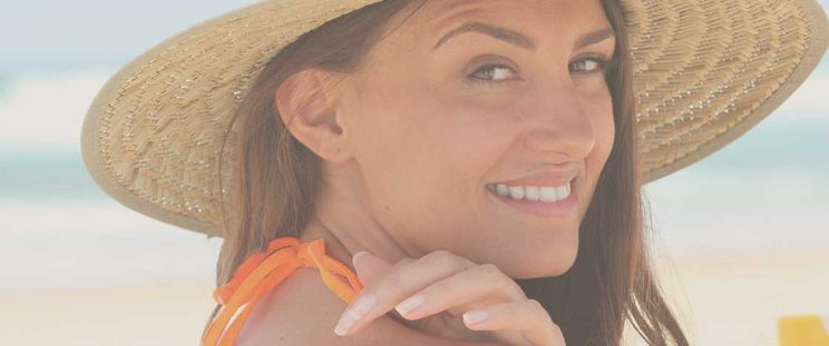 Girl wearing hat putting sunscreen on to avoid uneven skin tone by APT Medical Aeshetics