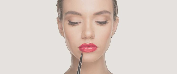 Beautiful woman applying red lipstick to show off lip injections by APT Medical Aesthetics
