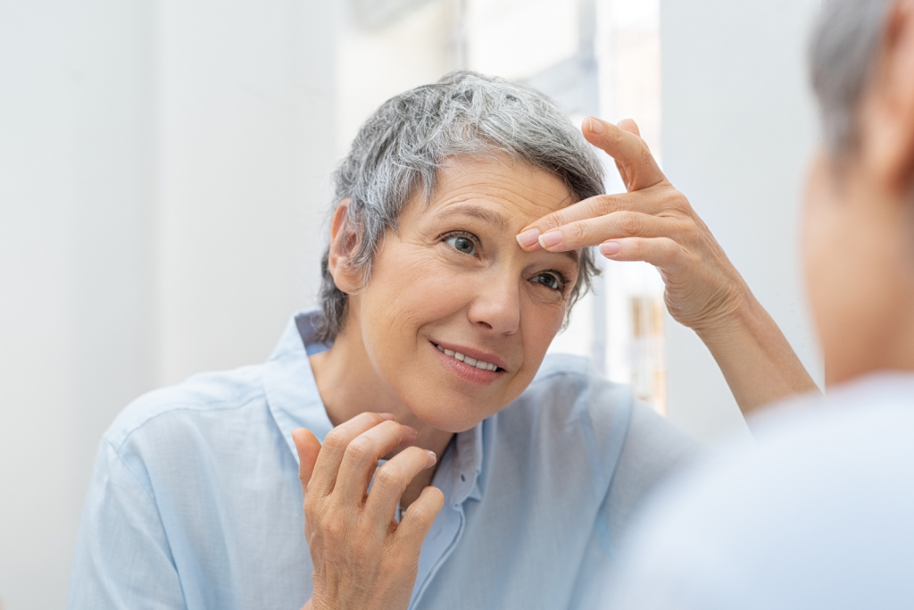 Mature woman looking at her wrinkles in a mirror