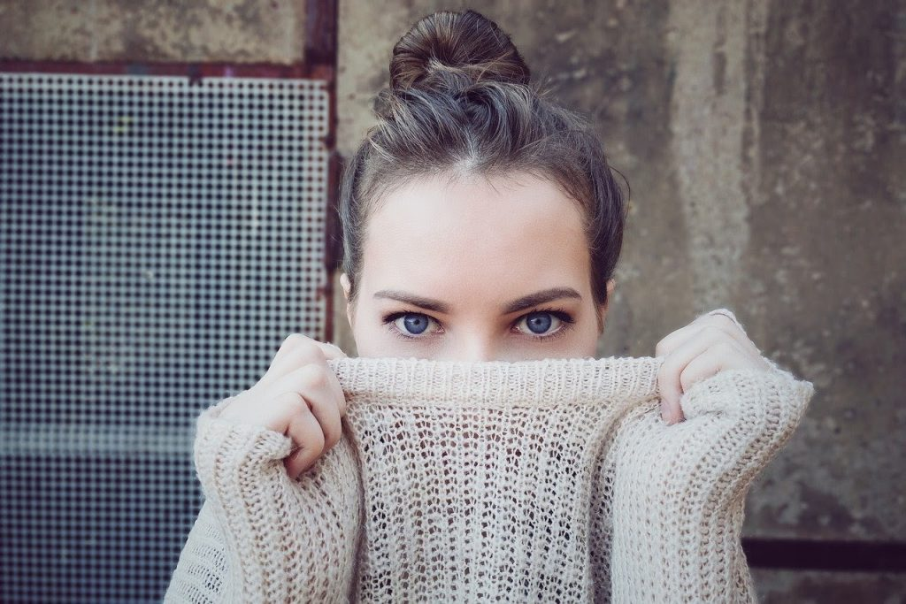 Fair-skinned woman with thick eyelashes and blue eyes, covering her face with sweater