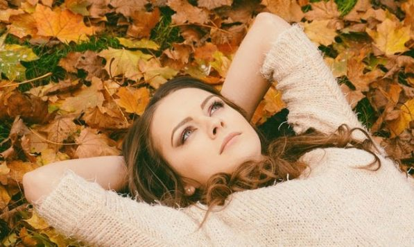 Woman lying down on the ground with autumn leaves