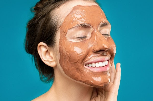 Woman with clay mask on her face