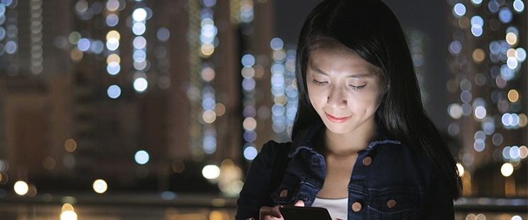 A woman stares at her illuminated phone screen at night