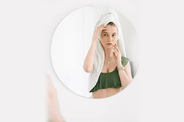 A young woman examines her skin in a mirror