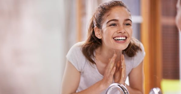 A woman washes her face in the morning