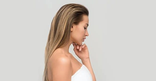 Profile view of a woman touching her face