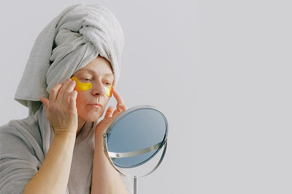 An older woman applies under-eye masks in the mirror