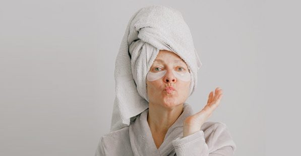 Older woman pouting for the camera dressed in a robe wearing under eye masks