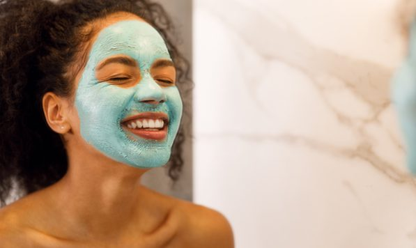 Beautiful woman smiling in a mirror with a skincare mask on