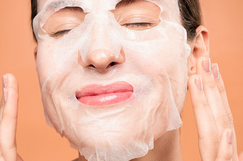 A woman using a hydrating face mask