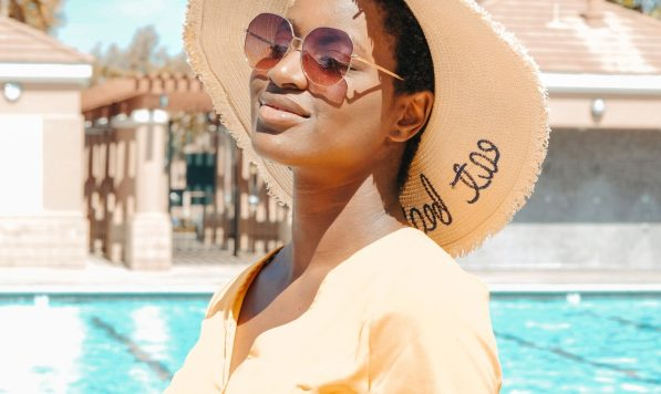 A woman standing by a pool with a hat and sunglasses on