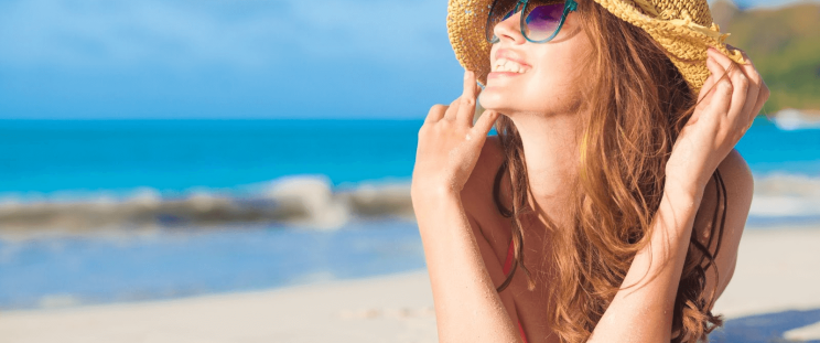 A smiling woman on the beach, under the sun