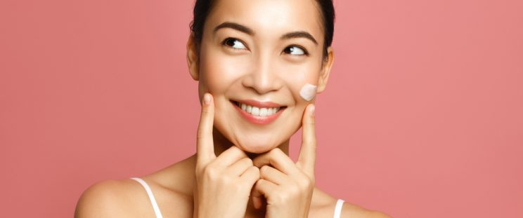 Happy, Asian woman using medical-grade skincare.